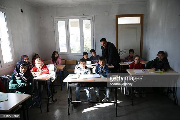 44yearsold Syrian refugee Hudur Omar Ilgeya lectures the refugee children at a temporary education center in Reyhanli District of Hatay Turkey on...