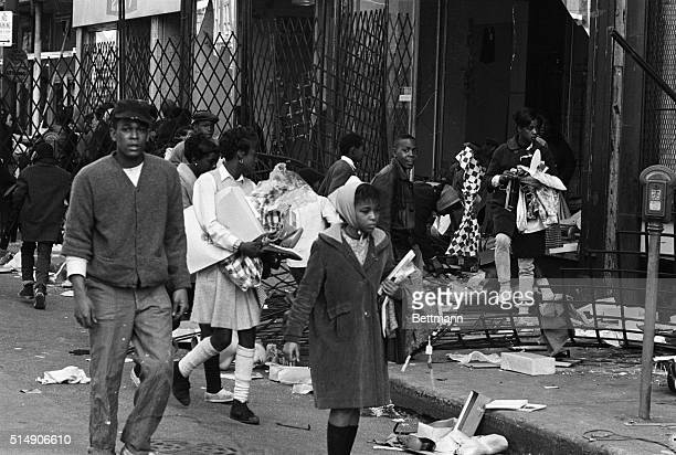 Youthful Negroes leave a store carrying all kinds of merchandise after ripping off the gates and breaking the windows on Chicago's west side 4/5 A...