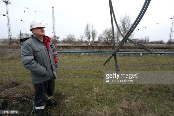 45yearold Ruslan Kolesov Director of transport at the Avdiivka Coke and Chemical Plant examines power lines damaged by shelling between Ukrainian...
