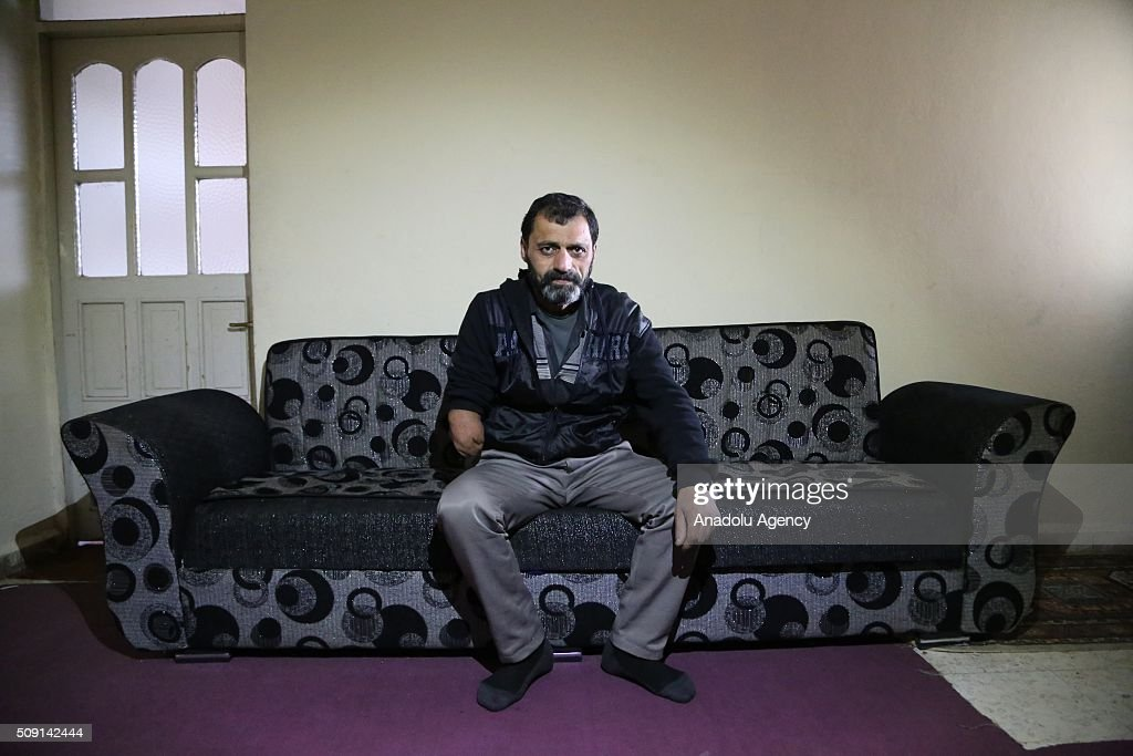 45-years-old Syrian refugee Hassan Ahmed Talib (C) fled from Syria due to ongoing civil-war, poses at a house in Turkey's Syrian border city Hatay's Reyhanli District on February 08, 2016. Hassan had lost half of his right arm due to Assad Regime's sniper assault. Turkey spent US$ 8 Billion and hosts approximately 2 million refugees.