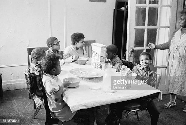 Mama looks on as six of the seven children sit down to a breakfast of corn flakes and milk in their apartment in New York's Harlem district The...