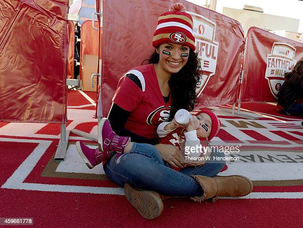 A 49ers fan and mother from Mexico feeds her baby prior to an NFL football game between the Seattle Seahawks and San Francisco 49ers at Levi's...