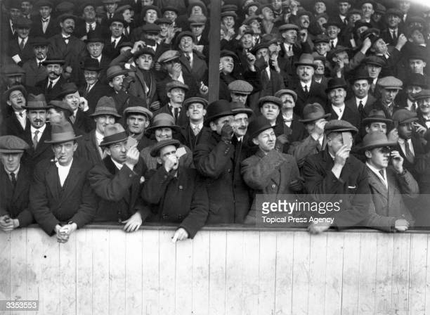 Spectators at Upton Park to see the football match between West Ham United and Aston Villa take a moment to view the eclipse of the sun during play