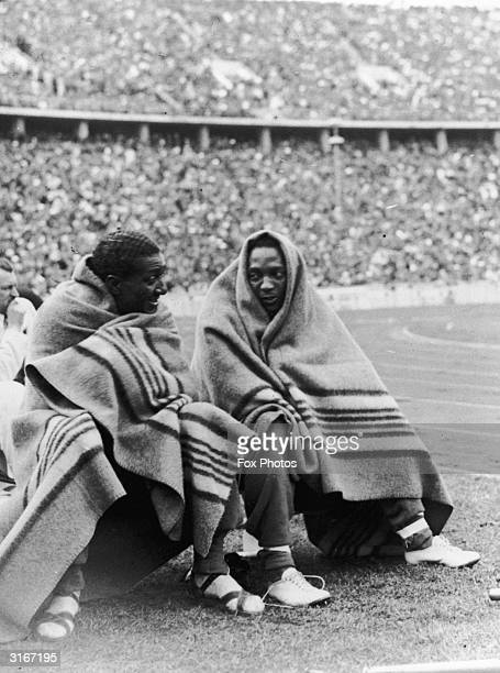 American athletes Jesse Owens and Ralph Metcalf keep warm under blankets during the 100 metres finals at the 1936 Berlin Olympic games The pair won...