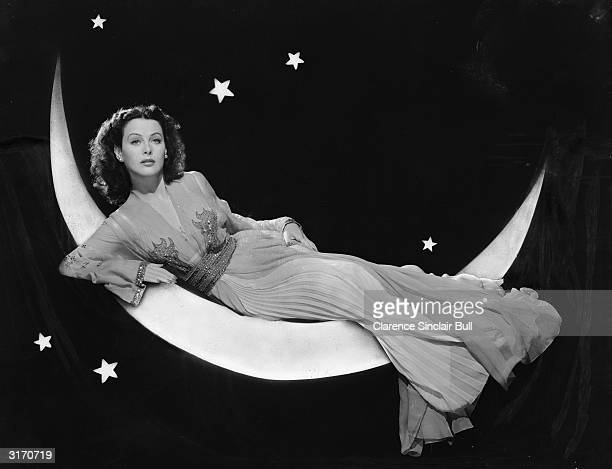 Austrian born actress Hedy Lamarr models a long flowing dress whilst reclining on a crescent moon in a publicity shot for her film 'The Heavenly Body'