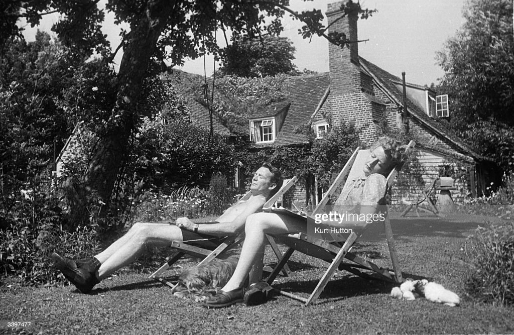 English actor John Mills and his wife playwright Mary Hayley-Bell sunbathing in the garden at their cottage in Denham village, England. Original Publication: Picture Post - 2059 - He Plays What She Writes - pub. 1945