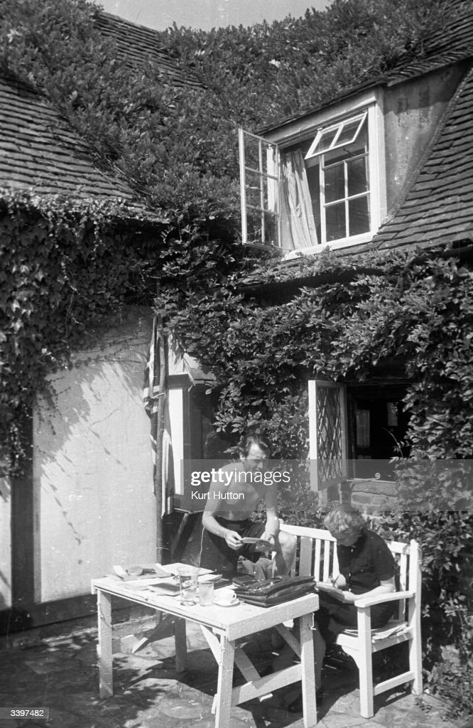 English actor John Mills dictating a letter to his wife playwright Mary Hayley-Bell in the garden of their cottage in Denham village, England. Original Publication: Picture Post - 2059 - He Plays What She Writes - pub. 1945