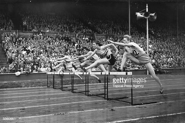 The 100 metre hurdles in the Olympic women's finals at Wembley Stadium Right to left Francina 'Fanny' BlankersKoen 1st Maureen A G Gardner 2nd Maria...