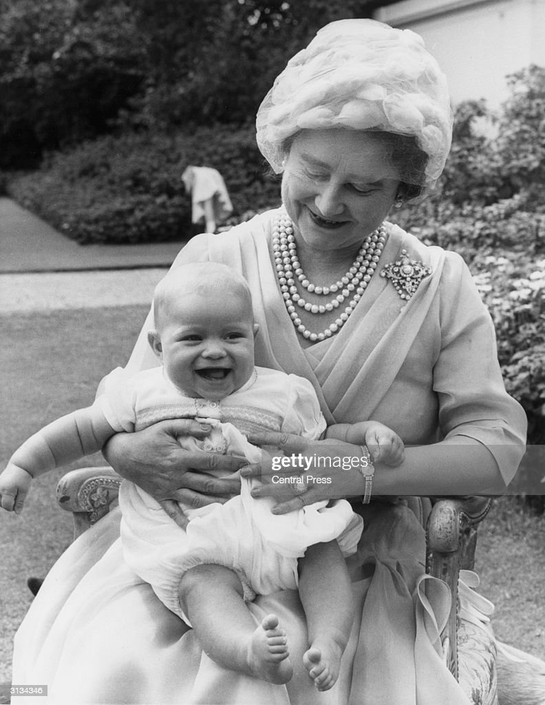 Elizabeth, the Queen Mother (1900 - 2002) holds her six-month-old grandchild Andrew on her lap during her 60th birthday celebrations at Clarence House, London.