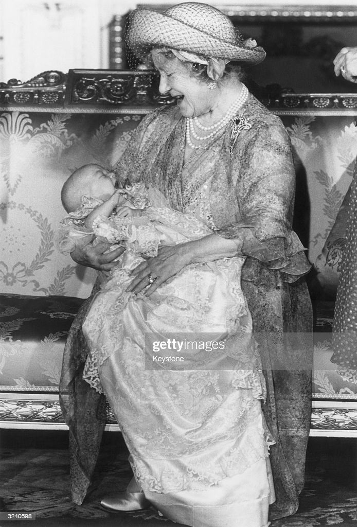 Queen Elizabeth, The Queen Mother (1900 - 2002), holding baby Prince William after his baptism at Buckingham Palace. He is wearing the Royal Christening Robe.