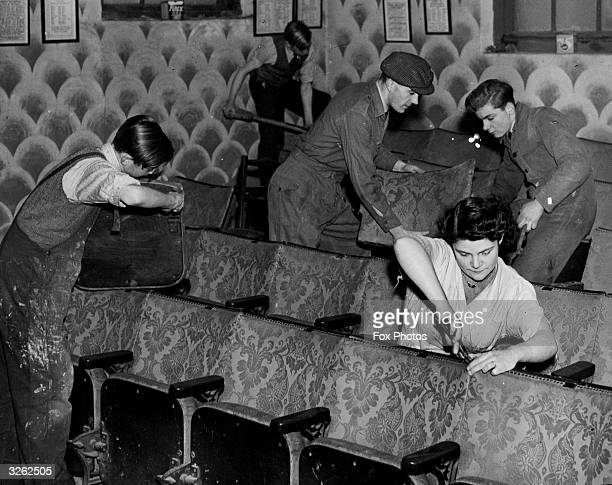 Members of an amateur dramatics society called the Incognito Players installing old cinema seats in the theatre they are building themselves