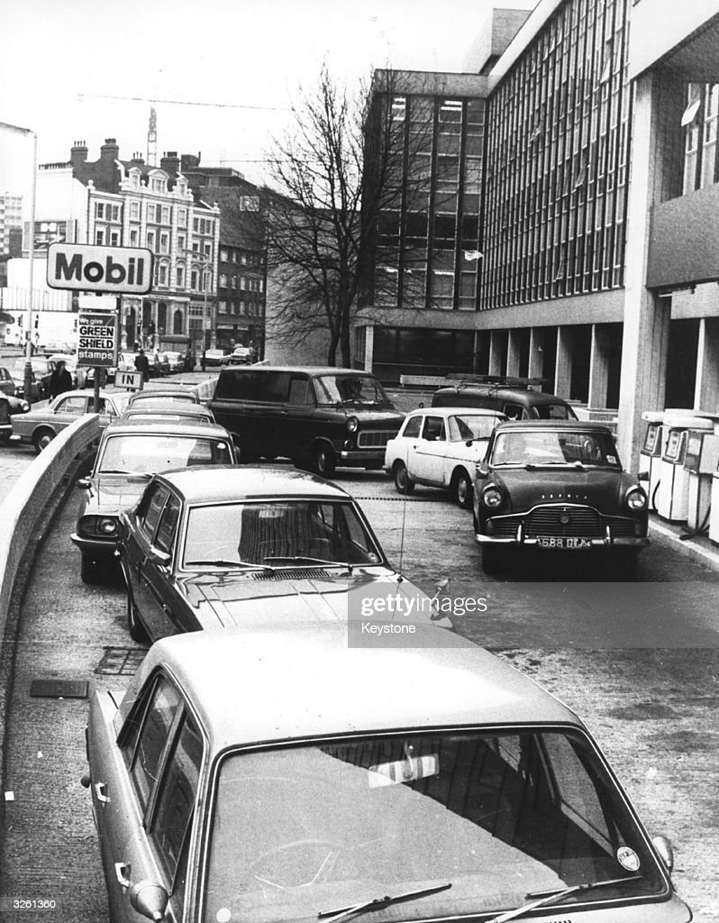 Pedestrians walk by as motorists queue up for petrol at a garage at Waterloo during the great petrol shortage of 1973. Chaos and traffic jams ensued as they scrambled and formed long queues at petrol filling stations.