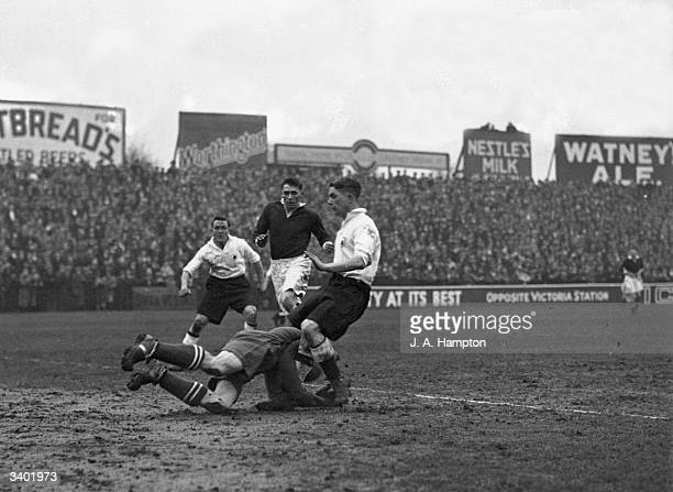Millwall goalkeeper Wilson dives bravley to take the ball from the feet of Fulham's onrushing Johnny Price during a match between Fulham and Millwall...