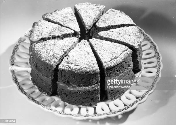 A large cake cut into slices spread with filling and sprinkled with icing sugar
