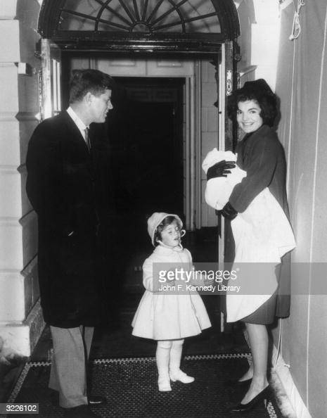 US President John F Kennedy smiles as he stands with his wife First Lady Jacqueline Bouvier Kennedy and their daughter Caroline in front of a doorway...