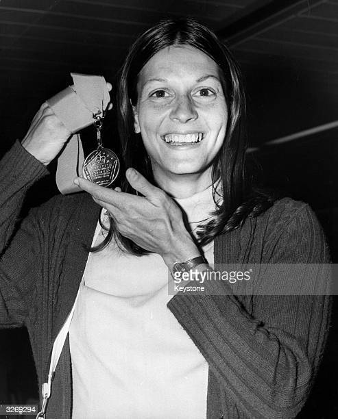 Judy Vernon British 100 metres hurdles champion holding her Commonwealth gold medal at London's Heathrow Airport on her return from New Zealand