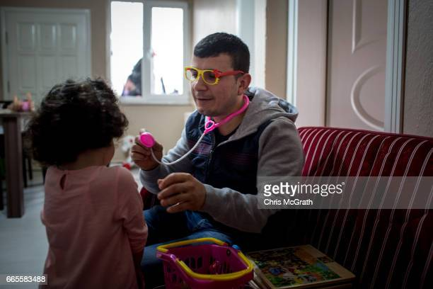 4th generation coal miner Sezai Aydin plays a doctors game with his daughter Berra after arriving home from working his shift at a small coal mine on...