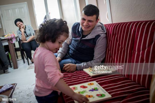 4th generation coal miner Sezai Aydin plays a game with his daughter Berra after arriving home from working his shift at a small coal mine on April 5...