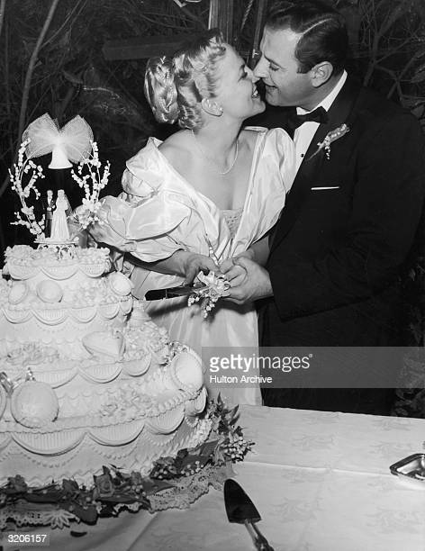American singer and actor Peggy Lee and actor Bradford Dexter kiss and cut the first slice of their wedding cake in the tentcovered garden of Lee's...