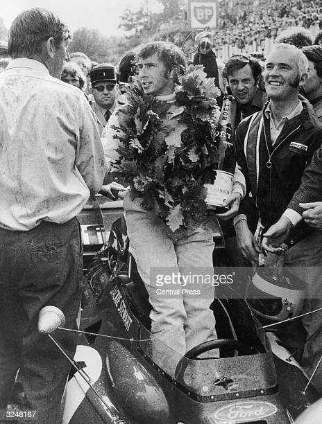 Scottish world champion racing driver Jackie Stewart with a wreath of oak leaves and a bottle of cham[pagne after his victory in the French Grand...