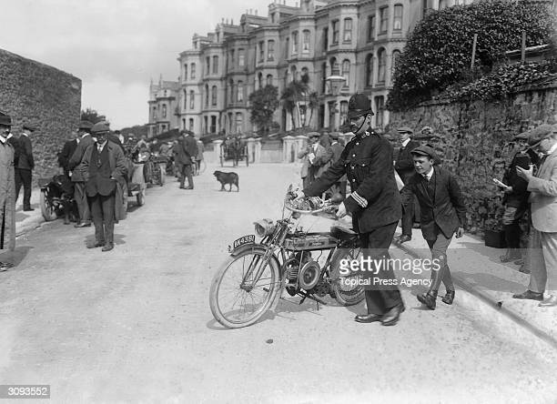 A policeman moves a motorcycle to clear a way for the traffic during the Isle of Man Tourist Trophy Race