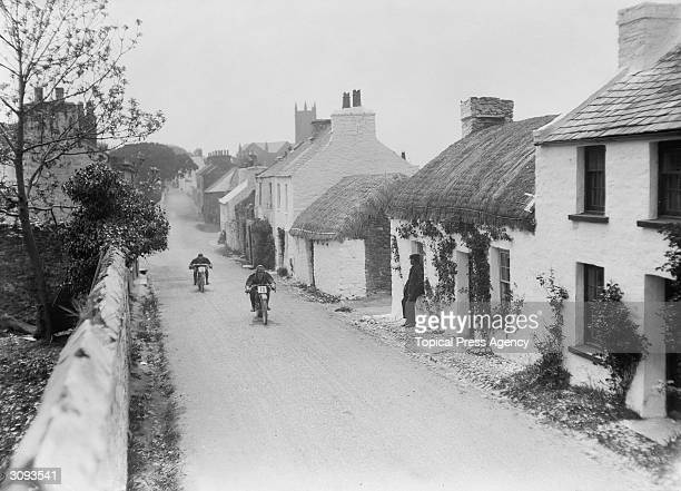 Tom Peek on a Peelers and W Creyton on an Ariel passing through Kirk Michael village during the Isle of Man Tourist Trophy Race