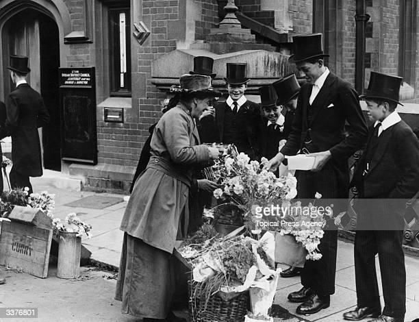 Pupils of Eton College buying flowers from a street trader on the 4th of June a traditional day of celebrations at the school