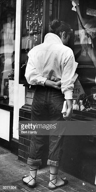 A fashionable young woman window shopping in London's Piccadilly Original Publication Picture Post 6576 What Makes Piccadilly pub 1953