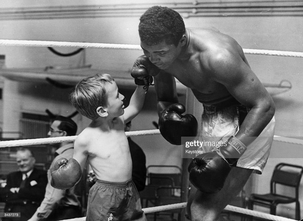 American heavyweight boxer Cassius Clay in a one round nontitle fight with 6 year old Patrick Power Young Patrick is taking boxing lessons in order...