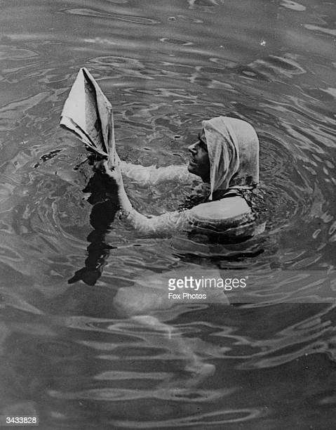 Miss Mercedes Gleitye her head covered with a damp towel reads a newspaper as she keeps cool in the water