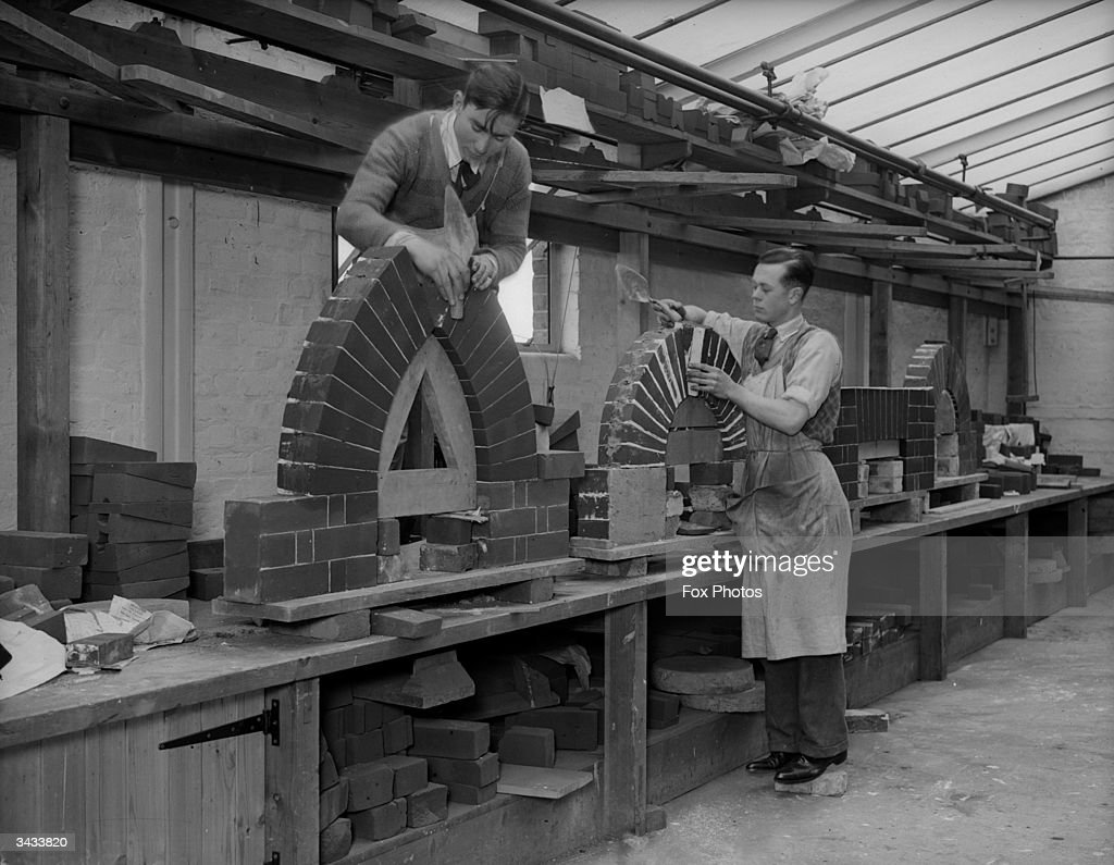 Trainees at an LCC (London County Council) School of Building at Ferndale Road, Brixton are constructing brick fireplaces.