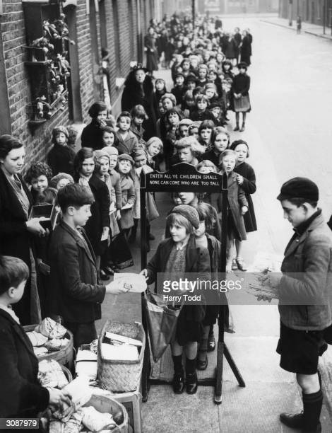 At the Fern Street settlement in Bow east London only children who are small enough can get a weekly parcel of toys for a farthing An archway is set...