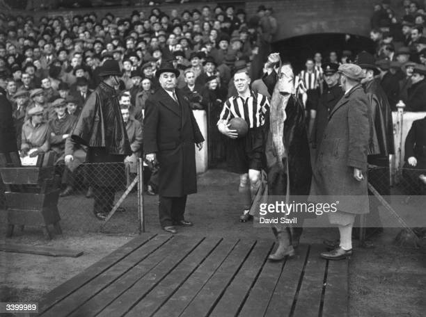 Grimsby Town FC team captain Hall leads his team out on to the pitch As the team emerge a supporter waves a cod at his side in honour of Grimsby's...