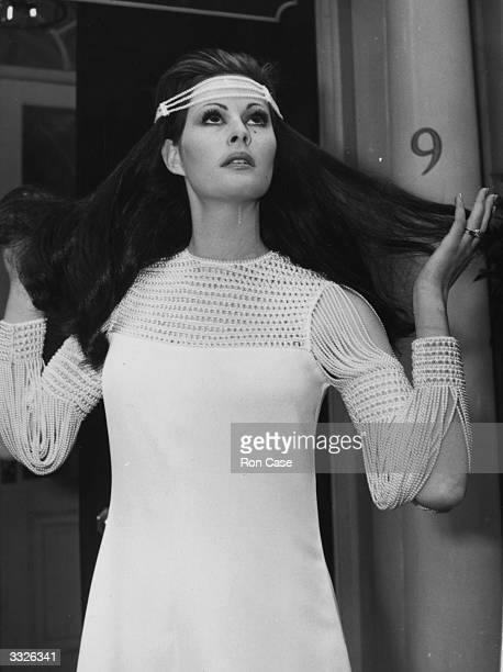 'Isadora Duncan' a white crepe evening dress with pearl sleeves and matching 'scarfhat' worn by Shula Tavet from the Spring Collection at Christian...