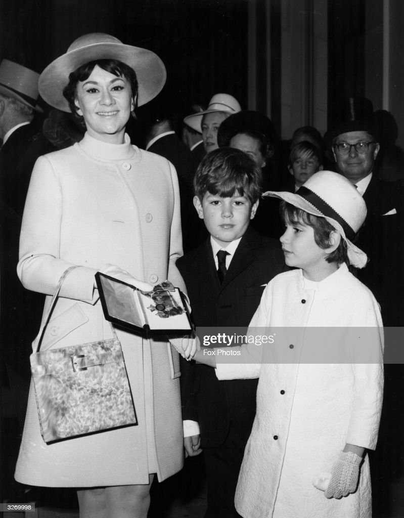 Actress, Joan Plowright, wife of Sir Laurence Olivier, with their two children, Richard and Tasmin, after the presentation of her CBE at Buckingham Palace.