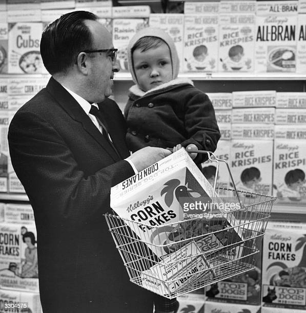A father holds his baby on one arm and the Kellogg's Cornflakes on the other whilst shopping at a Foodtown Supermarket in Lewisham London