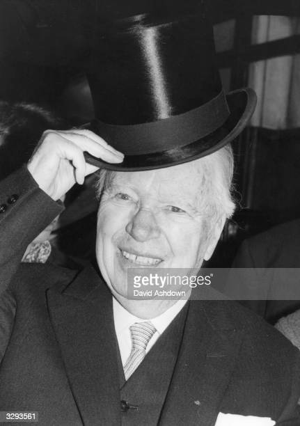 Film comedian Charles Chaplin lifts his hat as he leaves London's Savoy Hotel to go to Buckingham Palace to receive his knighthood from the Queen