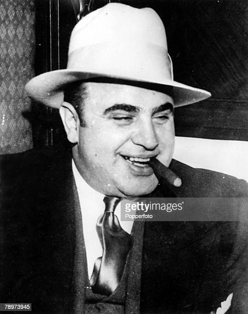4th May 1932 Chicago USA American prohibitiontime gangster Al Capone smiles as he smokes a cigar on his way to Atlanta Federal Penitentiary after...