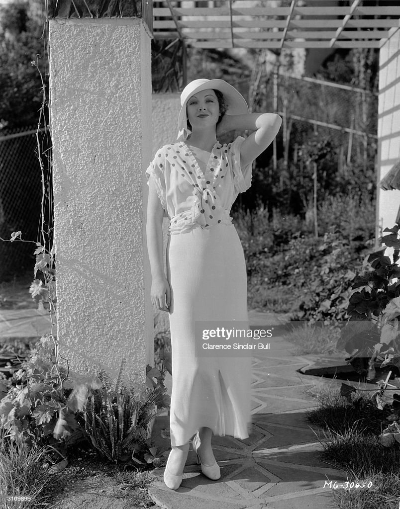 American actress Myrna Loy (1905 - 1993) wearing an ankle length dress and sun hat.