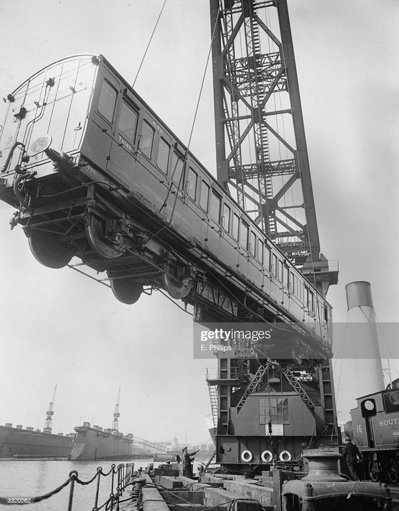 A floating crane at Southampton dock lifts on board one of the railway carriages being shipped to the Isle of Wight for the summer.