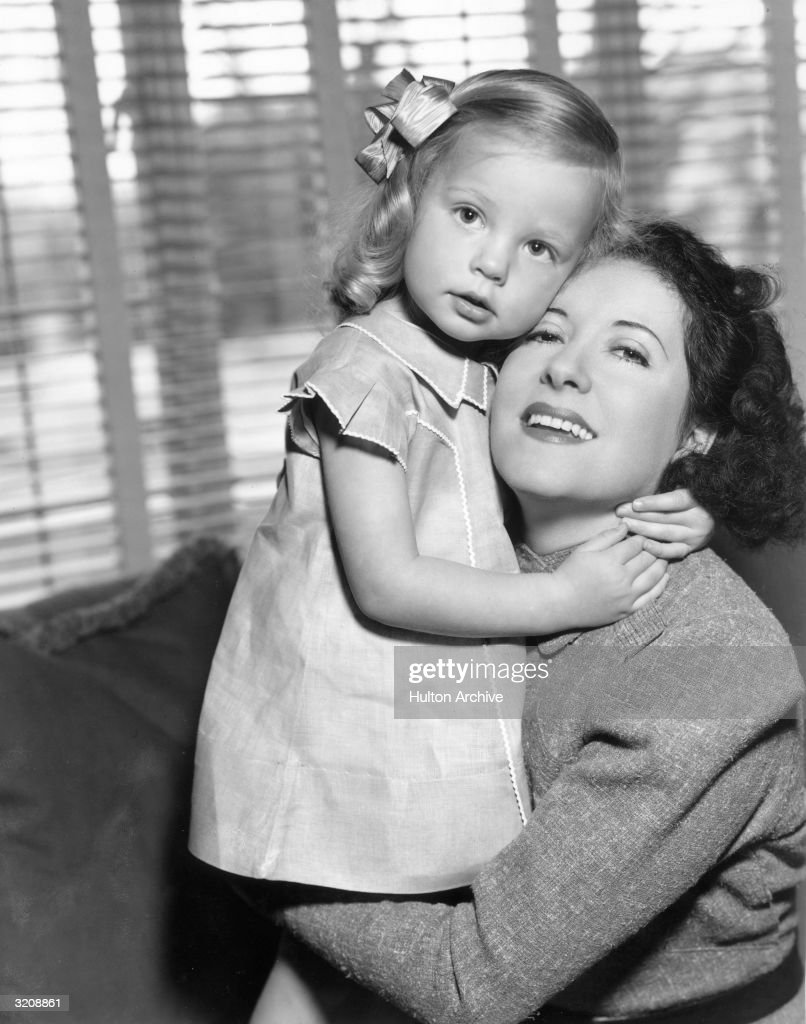 Portrait of American comedian and actor Gracie Allen holding her 3yearold daughter by George Burns Sandra Burns