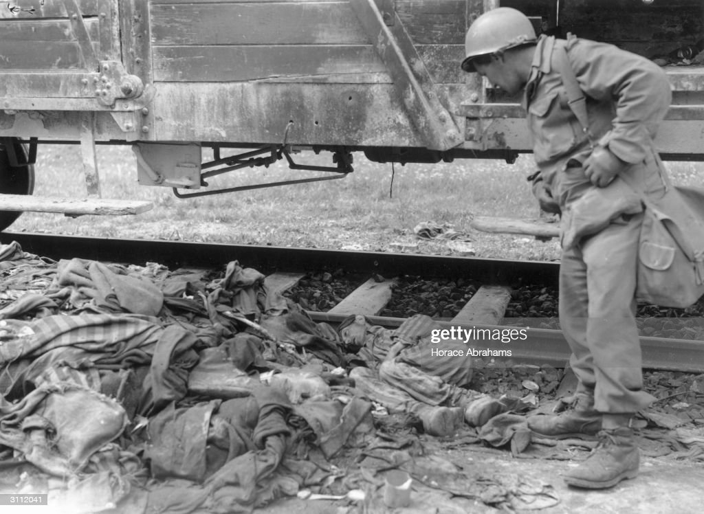 A soldier of the 42nd Rainbow Division of the US 7th Army discovers prisoners in striped garb, dead by the side of a death train, after liberating the Dachau Camp.