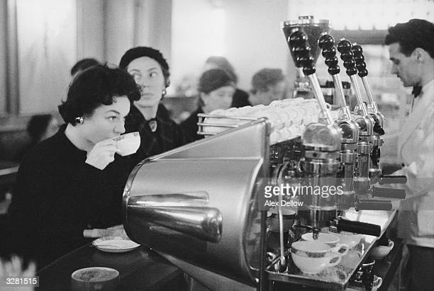 A customer contentedly sips her coffee in front of a gleaming coffeemaker in one of London's thriving coffee bars Original Publication Picture Post...