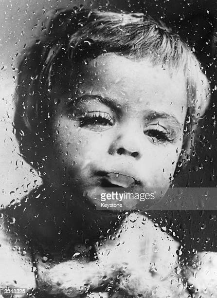 A Dutch boy studies the raindrops that pour down the outside a window