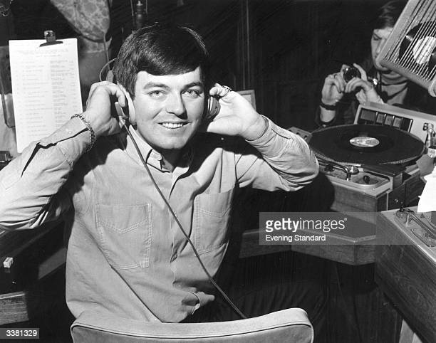Discjockey Tony Blackburn adjusting his headphones at the opening of BBC Radio's pop music station Radio 1