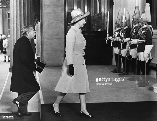 Queen Elizabeth II and the Emperor Hirohito walk past a guard of honour as they enter Buckingham Palace on the occasion of a three day visit to...