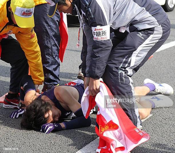4th runner of Komazawa University Kazuhiro Kuga lies on the ground after competing during day one of the 88th Hakone Ekiden on January 2 2012 in...