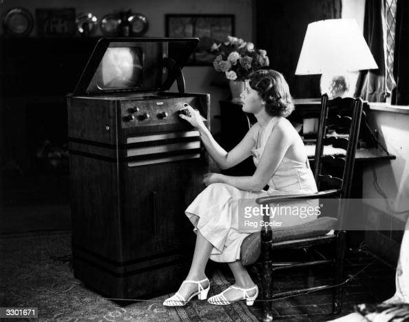 BBC Television announcer Jasmine Bligh tuning in a Baird 'televisor' at a cottage in Weald near Sevenoaks Kent