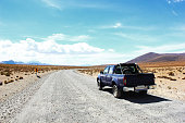 dark blue Car with Four Wheel Drive on Gravel Road through the Atacama Desert in the Lauca National Park, Andes