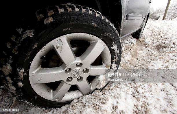 A 4x4 car fitted with all season tyres drives in snow beside the B3139 in the village of Horrington near Wells on January 23 2013 in Somerset England...